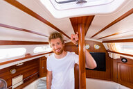 Young man in sailboat cabin, portrait - CUF49596