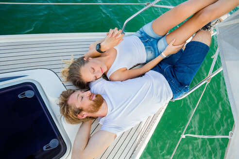 Young couple lying on sailboat on Chiemsee lake, overhead view, Bavaria, Germany - CUF49608