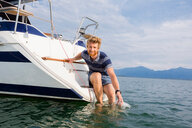 Young man leaning from sailboat on Chiemsee lake, portrait, Bavaria, Germany - CUF49617