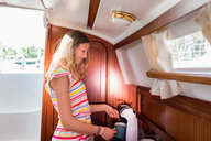 Young woman in sailboat cabin using coffee machine - CUF49629