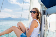 Young woman wearing sunglasses on sailboat on Chiemsee lake, portrait, Bavaria, Germany - CUF49635