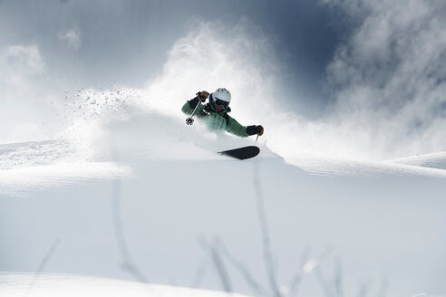Male skier speeding down snow covered mountain, Alpe-d'Huez, Rhone-Alpes, France - CUF49656