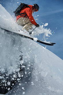 Male skier skiing mid air down steep snow covered mountain, Alpe-d'Huez, Rhone-Alpes, France - CUF49662