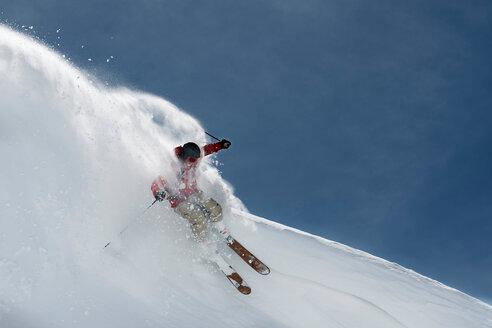 Male skier skiing down steep mountainside, Alpe-d'Huez, Rhone-Alpes, France - CUF49671