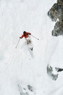 Male skier skiing down vertical mountainside, Alpe-d'Huez, Rhone-Alpes, France - CUF49674