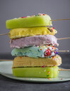 Close-up of colorful popsicles stacked in plate on table - CAVF63034