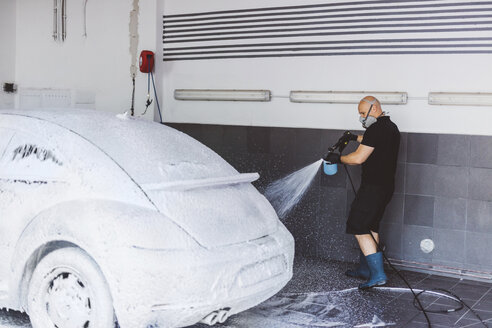 Side view of worker pouring water on car in workshop - CAVF63067