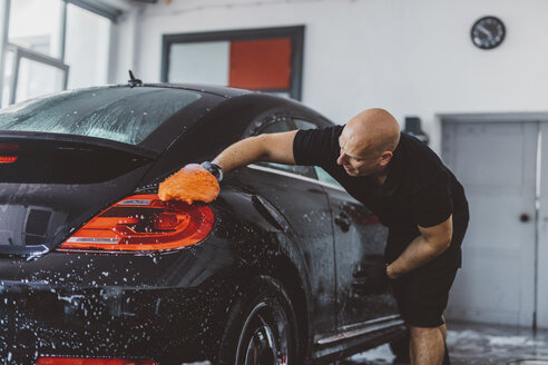 Side view of worker washing car with sponge while standing in workshop - CAVF63070