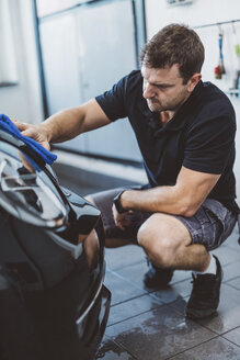 Male worker cleaning car with towel while crouching in workshop - CAVF63085