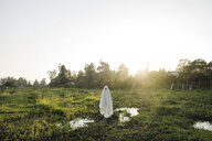 Man in ghost costume standing on grassy field against clear sky during sunset - CAVF63094
