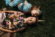 High angle view of sisters in Halloween costumes lying on grassy field in park - CAVF63109