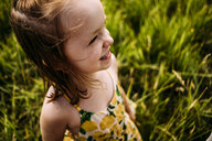 High angle view of smiling cute girl standing on grassy field - CAVF63112
