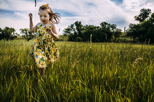 Cute girl walking on grassy field against cloudy sky - CAVF63115
