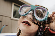 Close-up of cute girl wearing swimming goggles in pool against sky - CAVF63118