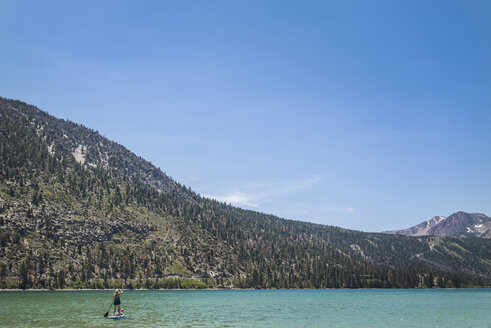 Mother paddleboarding with daughter in lake against mountains and sky during summer - CAVF63121