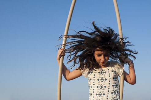 Girl with tousled hair playing against clear blue sky at playground - CAVF63133