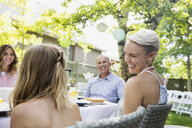 Smiling family enjoying garden party lunch - HEROF28383