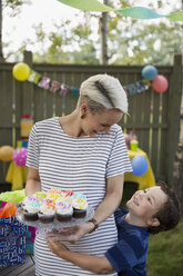 Son hugging mother holding cupcakes on cake stand - HEROF28395