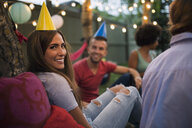 Portrait smiling woman party hat backyard birthday party - HEROF28401