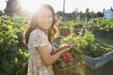 Smiling teenage girl harvesting vegetables in garden - HEROF28419