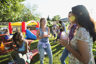 Women drinking and talking at sunny park party - HEROF28434