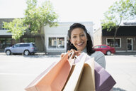 Portrait smiling woman with shopping bags sunny street - HEROF28461