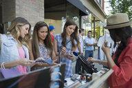 Women browsing merchandise at sidewalk sale - HEROF28467