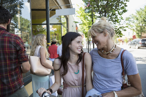 Smiling mother and daughter outside storefront - HEROF28470