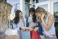 Women looking inside shopping bags at storefront - HEROF28482