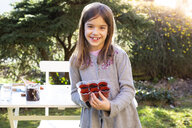 Portrait of happy little girl with flowerpots in the garden - LVF07860