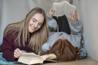 Two friends lying side by side on the floor reading books - LBF02411