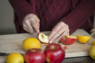 Hands of young woman cutting fruits on wooden board, close-up - LBF02417
