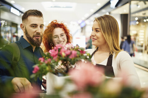 Shop assistant advising couple in flower shop - ZEDF01966