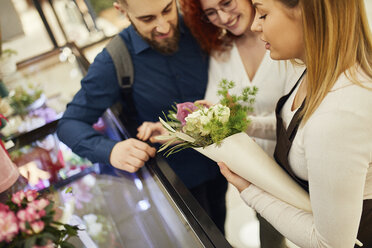 Florist wrapping flowers for couple in flower shop - ZEDF01969