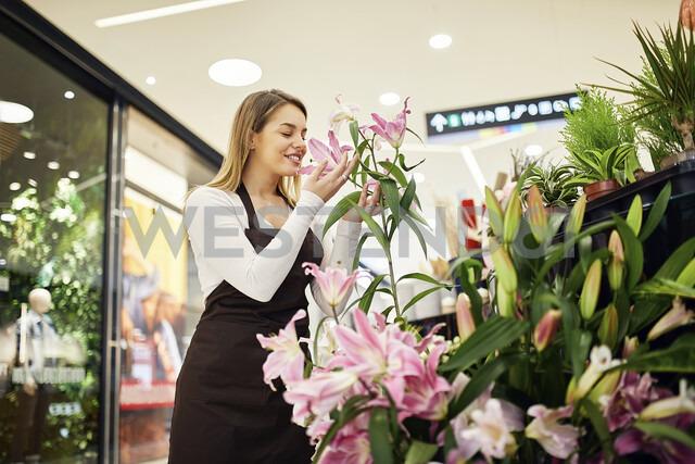 Florist smelling at flower in flower shop - ZEDF01972
