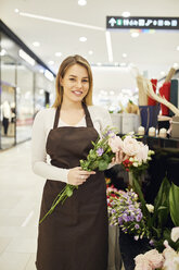 Portrait of smiling florist holding flowers in flower shop - ZEDF01978
