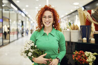 Portrait of smiling florist holding bunch of flowers in flower shop - ZEDF01984