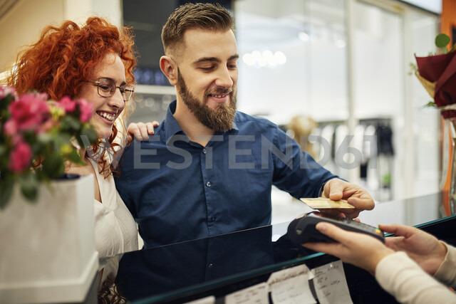 Happy couple paying at counter in flower shop - ZEDF01990 - Zeljko Dangubic/Westend61