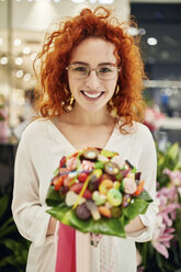Portrait of smiling woman holding candy bouquet in a shop - ZEDF01993
