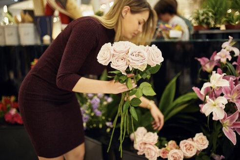 Woman arranging flowers in flower shop - ZEDF01996