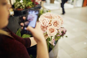 Close-up of woman holding bunch of roses in flower shop taking a cell phone picture - ZEDF01999