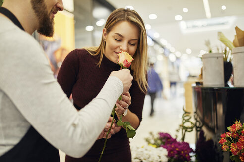 Florist letting customer smell at flower in flower shop - ZEDF02005
