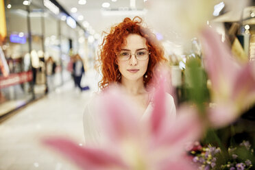 Portrait of redheaded woman behind blossom in a shopping arcade - ZEDF02011