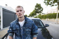 Portrait of young man in denim jacket standing in front of car - ABZF02253