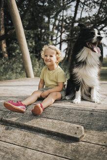 Netherlands, Schiermonnikoog, girl with Border Collie sitting on boardwalk in the forest - DWF00336