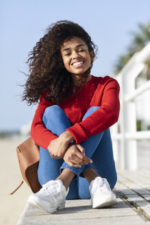 Portrait of happy young woman sitting on beach promenade - JSMF00810