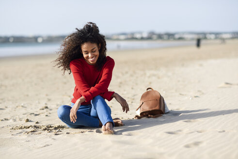 Spain, Andalusia, Puerto de Santa María, Happy young black woman with curly hair enjoying the beach sitting on the sand. Lifestyle and travel concepts. - JSMF00813