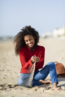 Happy young woman sitting on the beach - JSMF00816