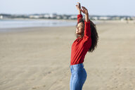 Happy young woman with raised arms standing on the beach - JSMF00819