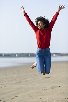 Carefree young woman jumping on the beach - JSMF00822
